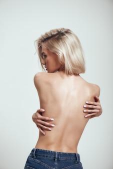 彼女の胸を覆うブロンドの髪を持つセクシーなスリムな女性の美しい体の裸の背中