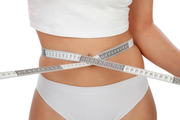 Beautiful body woman measuring her waist