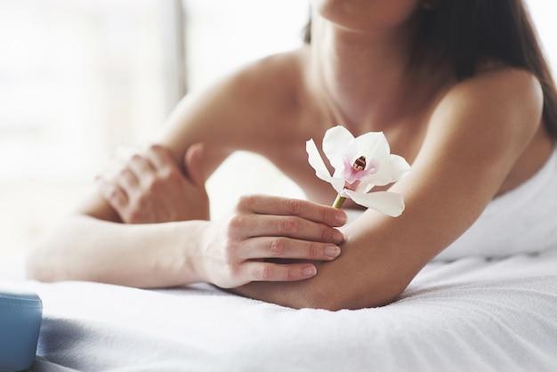 Красивое тело женщины с заботой тела и орхидеи белого цветка.