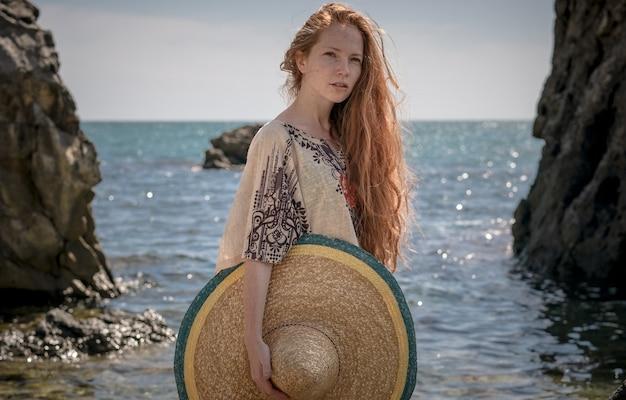 햇빛에 해변에서 포즈를 취하는 흰색 탑과 솜브레로를 입고 아름다운 boho 스타일의 모델