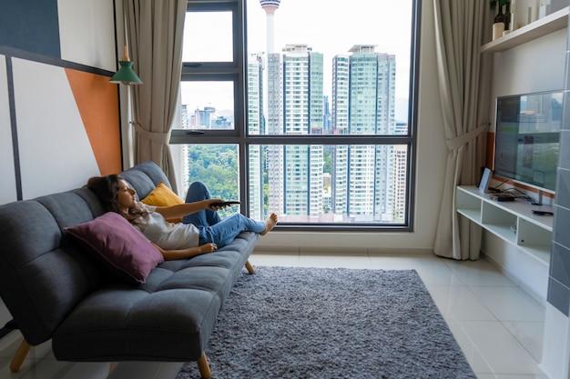 세련 된 인테리어에 소파에 아름 다운 지 루 갈색 머리 소녀는 tv를보고있다. 리모컨으로 tv 채널을 전환합니다
