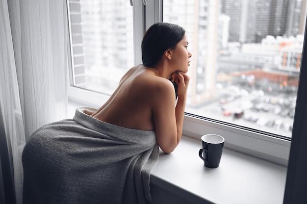 집에서 따뜻한 회색 담요 아래 창 창턱 옆에 앉아 아름 다운 지 루 날씬한 갈색 머리 여자. 코로나 바이러스 전염병 동안 자기 격리 검역. covid19 집 구하기 생명 개념