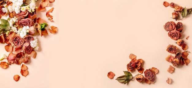 Красивая ботаническая композиция креативный макет с сухими лепестками цветов роз над бежевым столом. плоская планировка, копия пространства