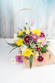 Beautiful bouquet in basket placed on burlap