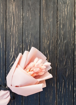 Beautiful bouquet of dry pink flowers on a wooden black background.