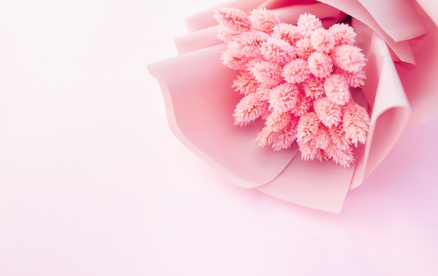 Beautiful bouquet of dry pink flowers on a wooden white background.