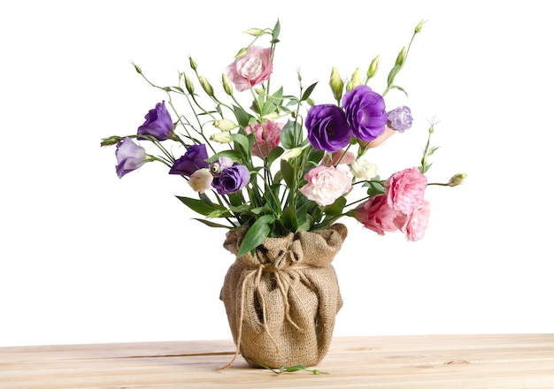 Beautiful bouquet of eustoma flowers in flowerpot on the wooden table