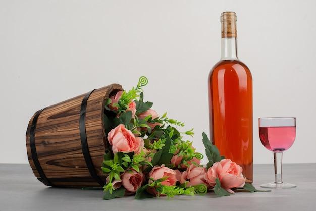 Bellissimo bouquet di fiori e una bottiglia di vino rosato sul tavolo grigio