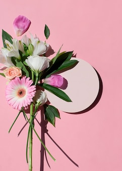 Beautiful bouquet of flowers bouquet of peonies roses gerberas with empty round mock up isolated on a pink background flat lay top view