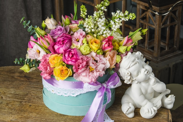 Beautiful bouquet of flowers and cupid statuette