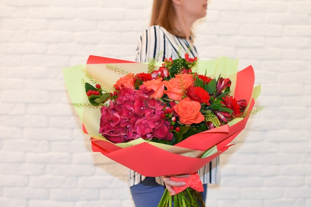 Beautiful bouquet of flowers in the hands. girl with large blooming bouquet.