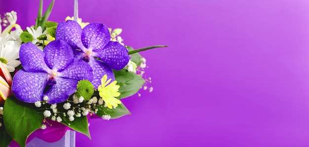 Beautiful bouquet of flowers in lilac wooden basket on purple background. orchids, chrysanthemums, lilies, chamomiles floral floristic composition. greeting card web banner with copy space