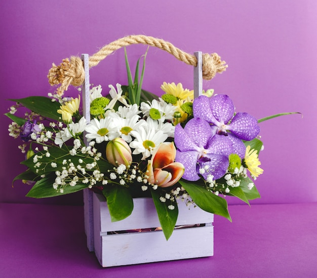 Beautiful bouquet of flowers in lilac wooden basket on purple background