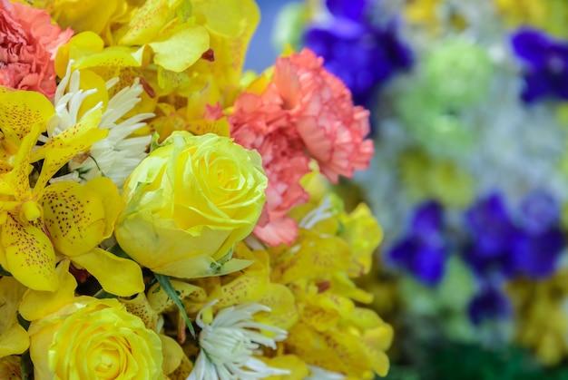 黄色いバラ、黄色い蘭、ピンクのカーネーション、白い菊の美しい花束の花