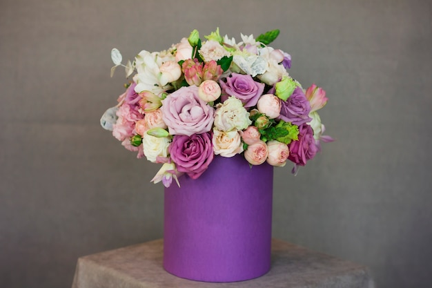 The beautiful bouquet of flowers in purple box on gray background