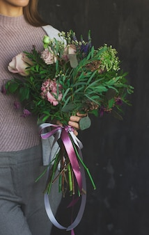 The beautiful bouquet of flowers in rustic style in hands of women