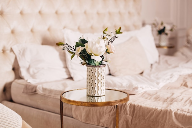 Beautiful bouquet of flowers in vase on bedroom background