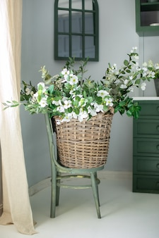 Beautiful bouquet of flowers in watering can on chair
