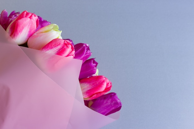 Beautiful bouquet of fresh colorful pink purple flowers on neutral background