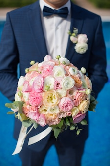 Beautiful bouquet of fresh flowers in the hands of the groom on the background of the pool at the hotel