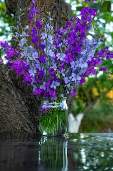 Beautiful bouquet of home flowers  blue and purple delphinium in a jar of water