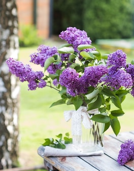 Beautiful bouquet of lilacs in a vase on wooden table in nature
