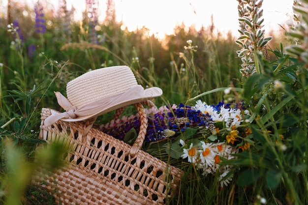 Beautiful bouquet of lupines lies in a bag together with a straw hat on the grass in the field.