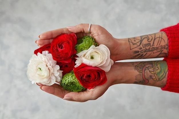회색 배경에 어린 소녀의 손에 다른 꽃으로 만든 아름다운 꽃다발. 다채로운 꽃을 섞습니다.
