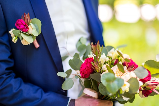 Beautiful bouquet mixed flowers in hands a groom in blue suit.