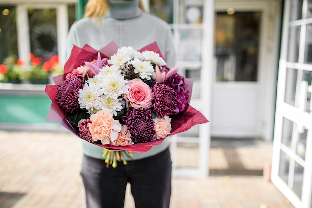 Beautiful bouquet of mixed flowers in womans hands. the work of the florist at a flower shop