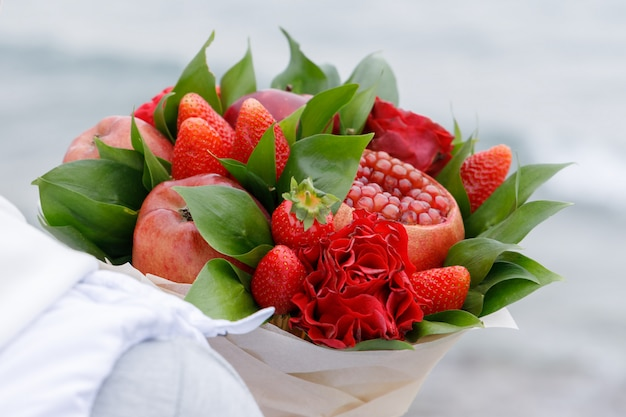 Красивый букет из яблок, граната, клубники и цветов