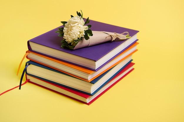 Красивый букет осенних цветов астры в крафтовой оберточной бумаге, перевязанной веревкой, лежащей на сложенных разноцветных книгах. день учителя концепция, литература, знания, образование. желтый фон копией пространства
