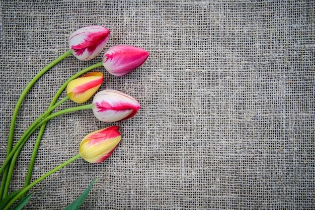 Красивый букет ярко-розовых и желтых разноцветных тюльпанов на фоне мешковины с копией пространства