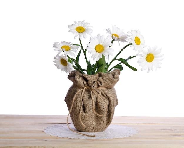 木製のテーブルの植木鉢にカモミールの花の美しい花束