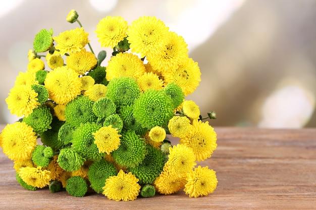 明るい背景に、木製のテーブルに菊の花の美しい花束