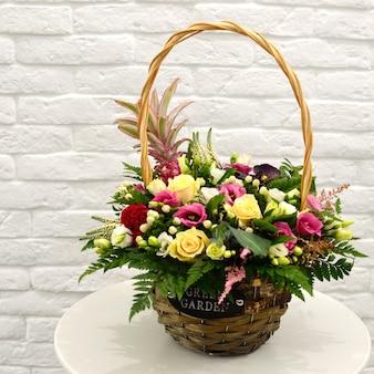 Красивый букет из разноцветных цветов в корзине на столе