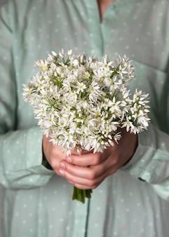 Красивый букет съедобных цветов дикого чеснока в руках девушки