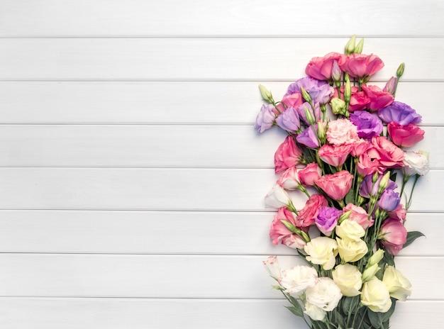 Красивый букет цветов эустомы на белом фоне деревянных. копировать пространство, вид сверху,