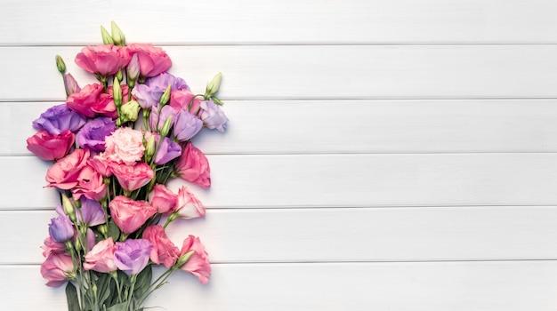 白い木の背景にトルコギキョウの花の美しい花束。コピースペース、上面図、