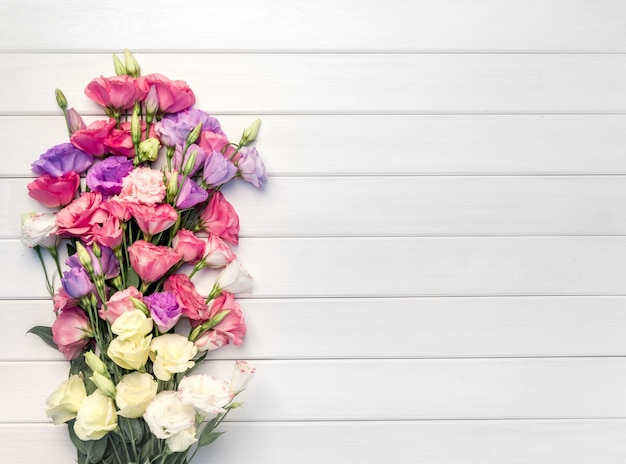 白い木製のテーブル、上面図にトルコギキョウの花の美しい花束