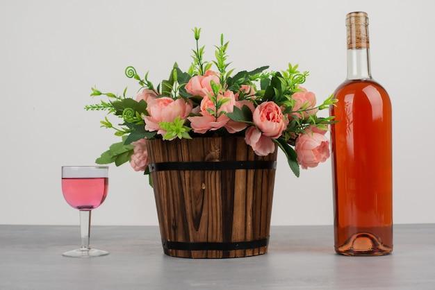 花の美しい花束と灰色のテーブルの上のロゼワインのボトル。