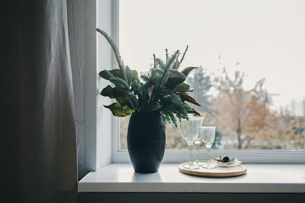 窓の花瓶に美しい花の花束。窓辺の空のグラス