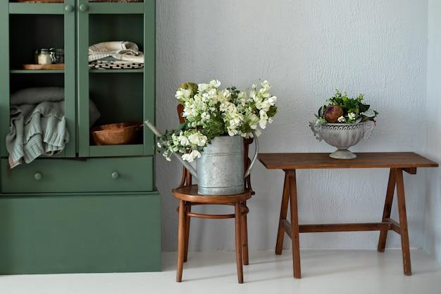 Красивый букет цветов в лейке на стуле