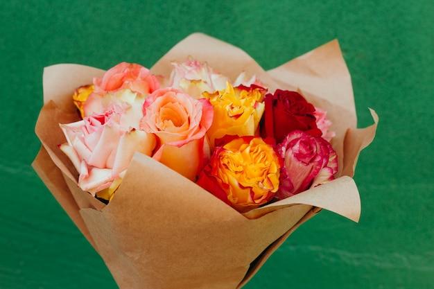 緑の壁の前にペーパークラフトで詰められた新鮮なカラフルなバラの美しい花束