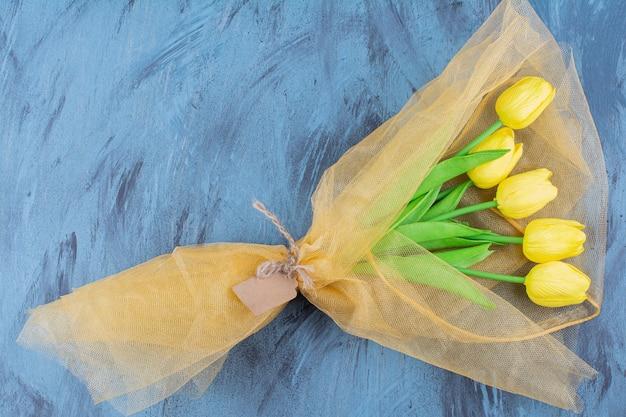 파란색에 신선한 노란색 튤립의 아름 다운 꽃다발입니다. 무료 사진