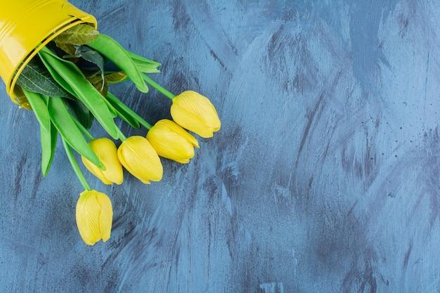 青に新鮮な黄色のチューリップの美しい花束。