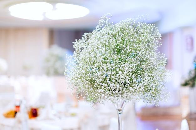 Красивый букет гипсофилы в прозрачной вазе на свадебном банкете