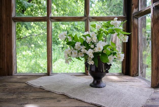Красивый букет веток жасмина в вазе у деревянного окна на природе