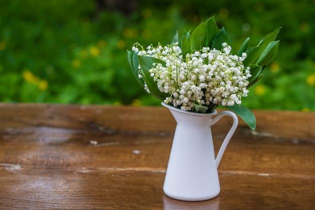 Красивый букет ландышей в белой эмалированной вазе на деревянном столе в саду, крупным планом