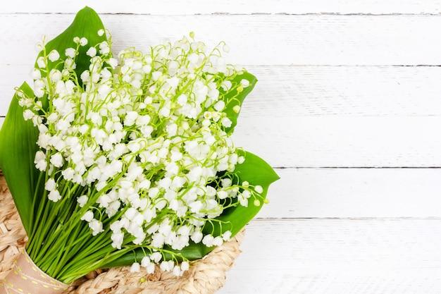 흰색 나무에 바구니에 은방울꽃 꽃의 아름다운 꽃다발
